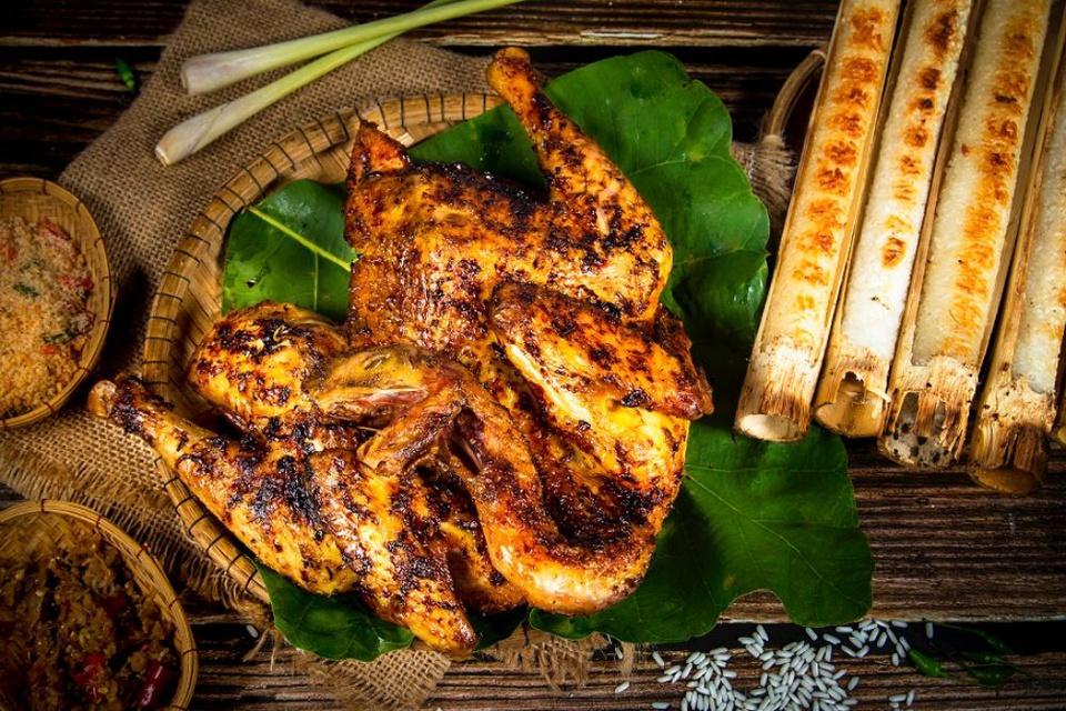 Buôn Đôn có đặc sản gà nướng Bản Đôn và cơm lam nổi tiếng. Gà nướng còn được gọi là gà sa lửa, thường được chế biến từ gà thả vườn sơ chế sạch, giữ nguyên con, tẩm ướp gia vị theo công thức đặc trưng của đồng bào dân tộc rồi kẹp vào thanh tre, cắm xuống đống than và nướng chín. Gà nướng ăn kèm cơm lam dẻo thơm, nấu trong ống nứa non. Ảnh: Bandontour.