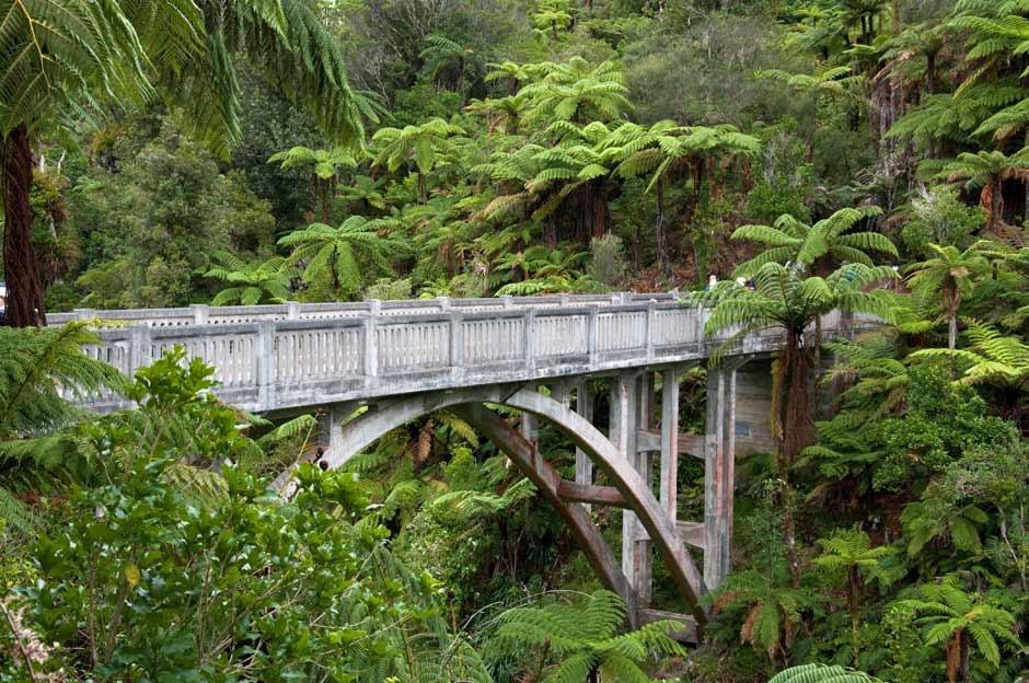 """Nằm sâu trong rừng của công viên quốc gia Whanganui (New Zealand), cây cầu bê tông này thu hút du khách nhờ vẻ ngoài khác lạ. Người dân địa phương và du khách gọi đây là """"cầu nối đến hư không"""". Năm 1917, cây cầu được xây dựng trên hẻm núi Mangapurua dẫn vào khu đất cấp cho những người lính trở về từ Thế chiến thứ nhất. Tuy nhiên, khu vực quá xa xôi và không phù hợp để trồng trọt nên dự án thất bại. Ảnh: NZHistory."""