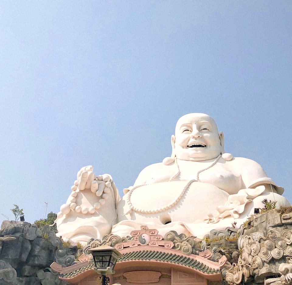 """Maitreya Buddha statue on the top of Cam Mountain belongs to Big Buddha Temple.  The statue has a height of nearly 34 m, clearly depicting a peaceful smile, compassion, equanimity and a characteristic big belly.  According to many experts, this statue achieves a high aesthetic level of architecture and harmony between the mountain and forest space.  The statue owns the title of """"The largest Maitreya Buddha on the top of the mountain in Vietnam"""" in 2006 and was recognized as the """"largest Maitreya Buddha statue on the mountain in Asia"""" in 2013. Photo: Tranvuvuong194."""
