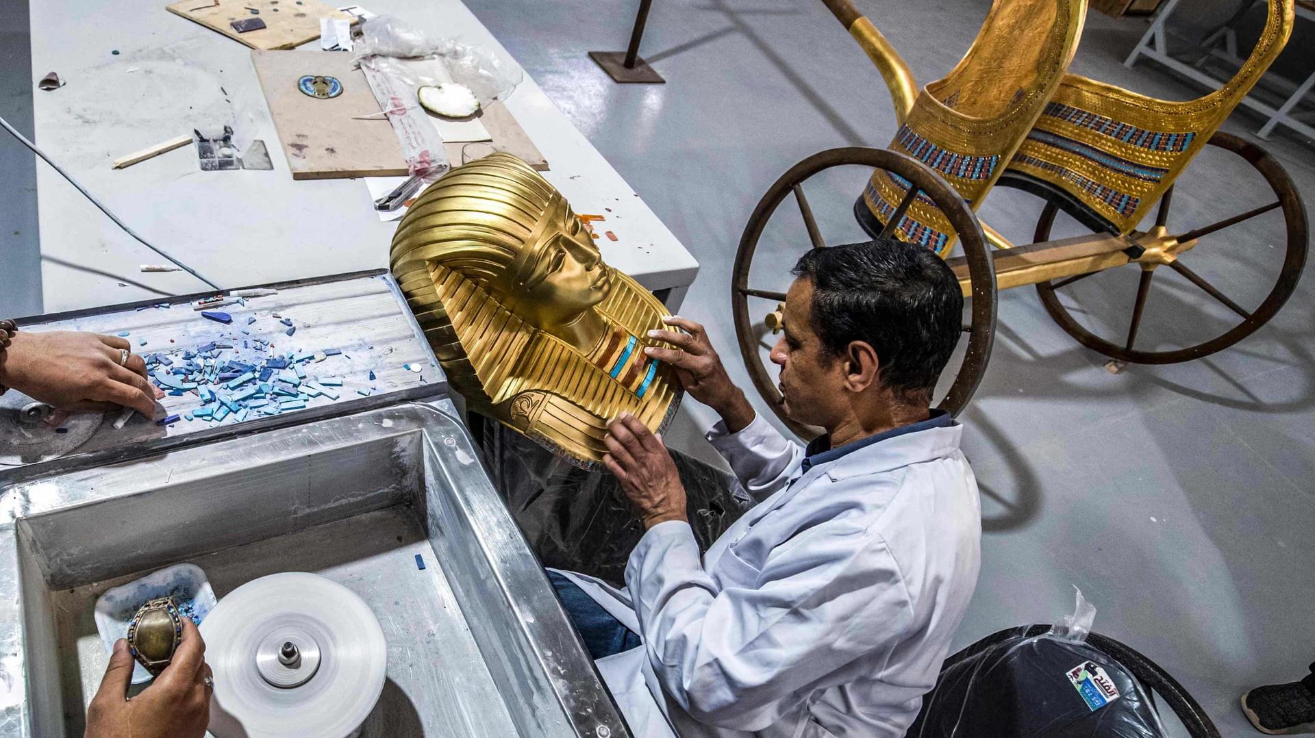 """Nhà máy Konouz (có nghĩa là """"Kho báu"""" trong tiếng Ả Rập) của chính phủ Ai Cập nằm ở Obour, phía đông thủ đô Cairo. Khuôn viên nhà máy có diện tích rộng 10.000 m2. Tại đây, các nghệ nhân tập trung sản xuất hàng nghìn bản sao cổ vật từ nhiều loại nguyên liệu, có thể kể đến như thạch cao, gỗ, đá, gốm, vàng..."""