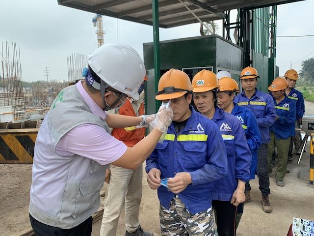 Do nhiệt độ cho công nhân trước khi xây dựng công trình.