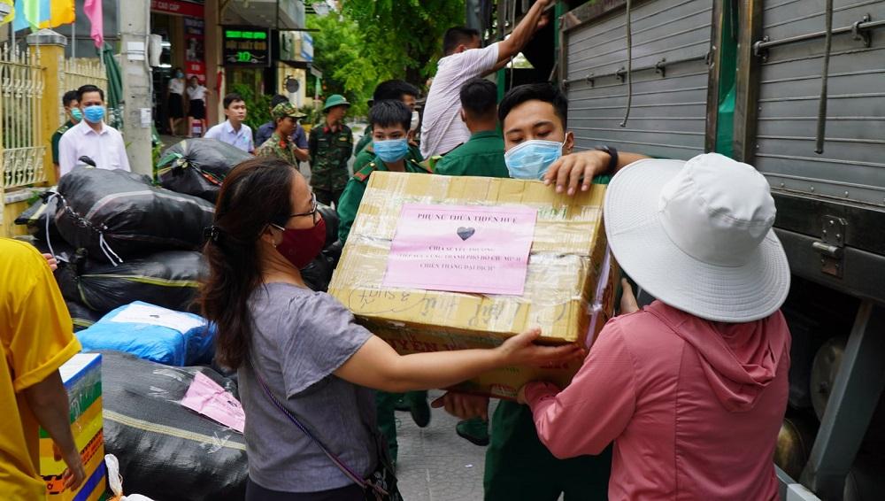 Người dân và lực lượng vũ trang cùng nhau vận chuyển lương thực, hàng hoá lên xe.