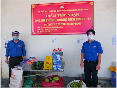 Bí thư Tỉnh Đoàn Trần Quốc Duy (bên phải) trao tặng rau, củ, quả tại chốt kiểm soát giao thông số 2 của tỉnh tại xã Tân Lập (H.Đồng Phú)