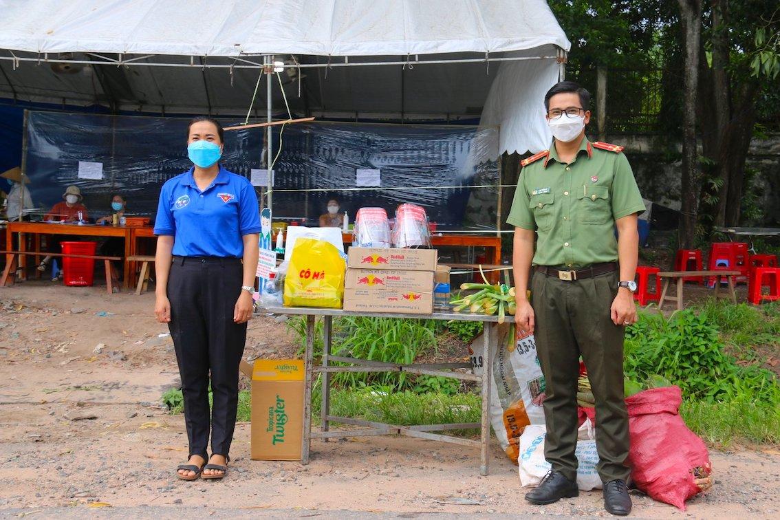 Thường trực BCH Đoàn Thanh niên Công an tỉnh - Thượng úy Lại Tiến Sĩ (bên phải) trao quà cho chốt kiểm soát liên ngành ở xã Minh Long (H.Chơn Thành)