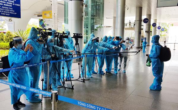 Các phóng viên tuân thủ giãn cách khi đưa tin các chuyến bay đưa người dân Đà Nẵng từ TP Hồ Chí Minh trở về