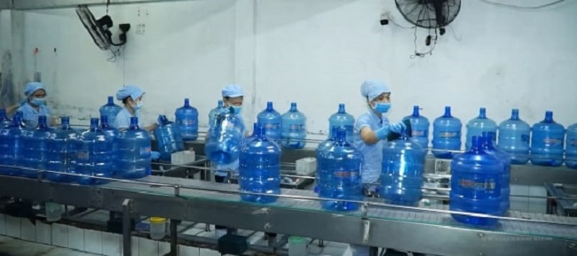 Công nhân mang khẩu trang, găng tay và giãn cách khi sản xuất.