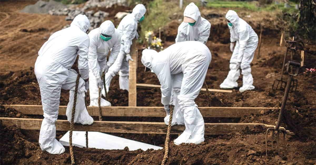 Các nhân viên nghĩa trang đang chôn cất thi thể bệnh nhân Covid-19 tại Indonesia. Ảnh: AFP.