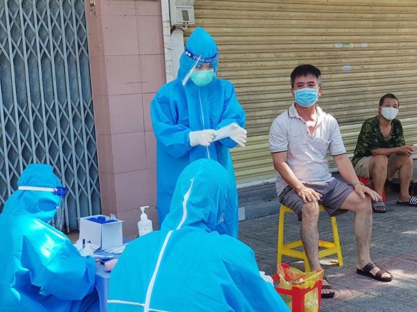 Nhân viên Trung tâm Y tế quận Thanh Khê thay găng tay mới trước mỗi lượt lấy mẫu xét nghiệm đại diện hộ gia đình
