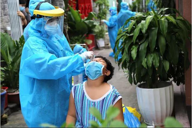 Cán bộ y tế TP Hồ Chí Minh lấy mẫu xét nghiệm cho một trẻ em tại cộng đồng. Ảnh: PLO.