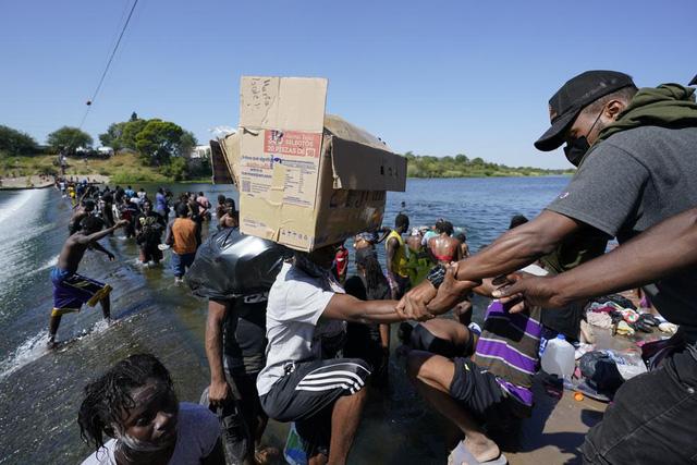 Người di cư Haiti băng qua một con đập để đến Mỹ từ Mexico ngày 17/9 ở Del Rio, Texas. (Ảnh: AP)