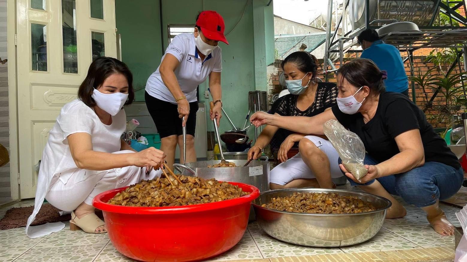 Bà Nguyễn Thị Bông - Chủ nhiệm CLB Sen Hồng (bìa trái) cùng bàTrần Thị Bông - thành viên CLB - Chủ Bếp cơm Nhà Bông, TX Phước Long (thứ 2, trái sang) đang làm món thịt kho để gửi tặng người dân về quê tránh dịch