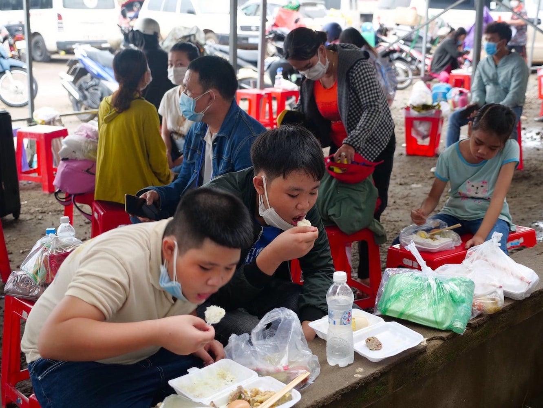 """Những đứa trẻ ngồi ăn thật ngon lành sau khi nhận các suất ăn miễn phí từ Tỉnh Đoàn và CLB Sen Hồng tại """"nhà chờ"""" ở chốt phòng chống dịch số 2 (H. Đồng Phú)"""
